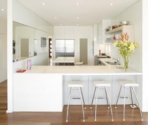 DOORS/PANELS Polyurethane two-pack gloss in Dulux Whisper White and Bristol Brimstone  BENCHTOP 40mm CaesarStone reconstituted stone in Osprey with waterfall end  SPLASHBACK Starfire glass with aluminium strip dividers in Dulux Whisper White  FLOOR Australian brush box floorboards