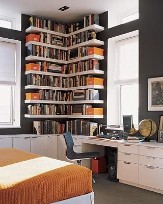 Corner bookshelves in in corner on door wall. Reading chair in front of it and sleek desk between door.