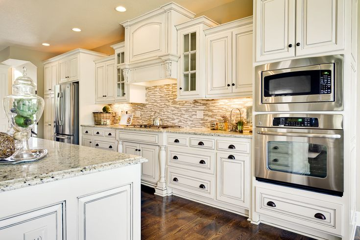 traditional White kitchen cabinets, tile backsplash, wood floors, granite countertops. I could live with this...