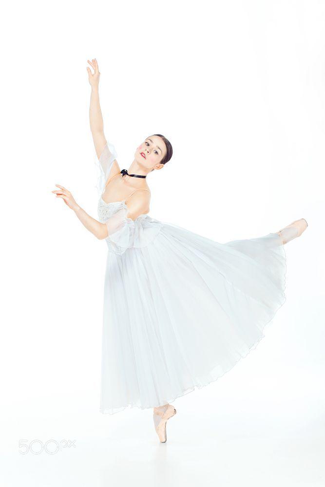 Ballerina in white dress posing on pointe shoes, studio background. by Volodymyr Melnyk on 500px