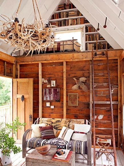 Salvaged items fill this adult tree house in Wisconsin. A ladder forms a railing for the loft filled with books. More about this property: http://www.midwestliving.com/homes/featured-homes/we-bought-a-camp/page/6/0