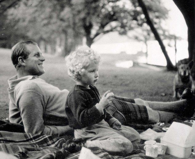 Prince Philip and a young Princess Anne relax in the grass during a picnic with a hopeful corgi dog in the background. But Prince Philip is said to 'loathe' the dogs as he thinks they are too 'yappy'