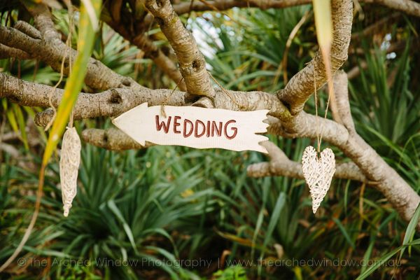 cute beach wedding sign hung from a tree branch. Photography by The Arched Window.