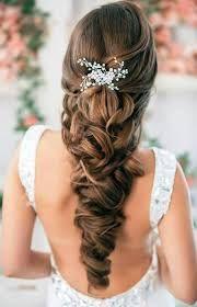 Cette jeune mariée aux longs cheveux porte une coiffure magnifique, ressemblant à une large tresse relâchée. Dans le haut de celle-ci, on re...