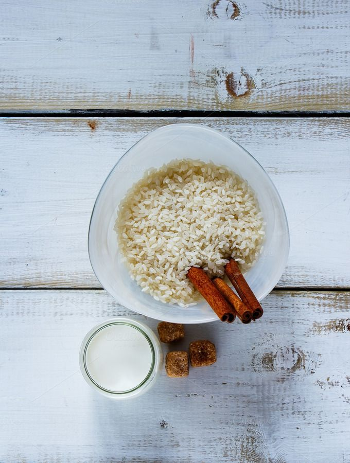 #Ingredients for making rice pudding  Top view of kitchen table with ingredients for making rice pudding. Bowl of white uncooked rice brown sugar cinnamon sticks and jug of milk or cream over old wooden background.