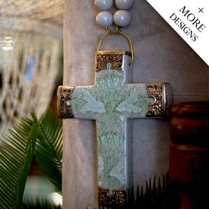 Description: Hand painted porcelain cross with antiqued filigree metal which encases the edges of the cross