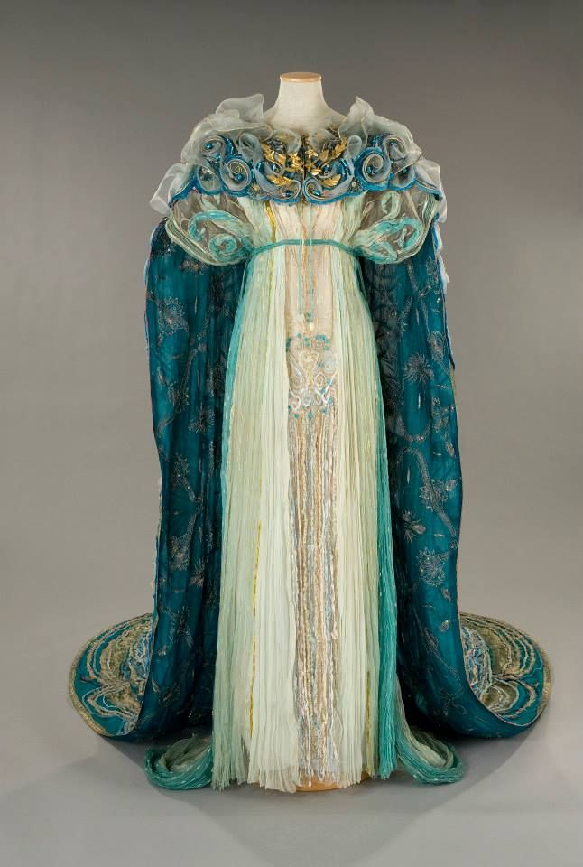 "Costume:Gabriella Pescucci in 1998. ""Queen Titania"". organza is in tones ranging from ivory to teal, with the central panel embroidered chenille yarns, golden threads and green stones.The mantle, with its interior of blue georgette fabric all gold and silver wire, consists on the combination of large edges and silk embroidered inserts with large pleated blue silk drapes. The embroidery, are a variety of materials including: chenille wires, wires gold, azure stones and nylon tulle. Front:"