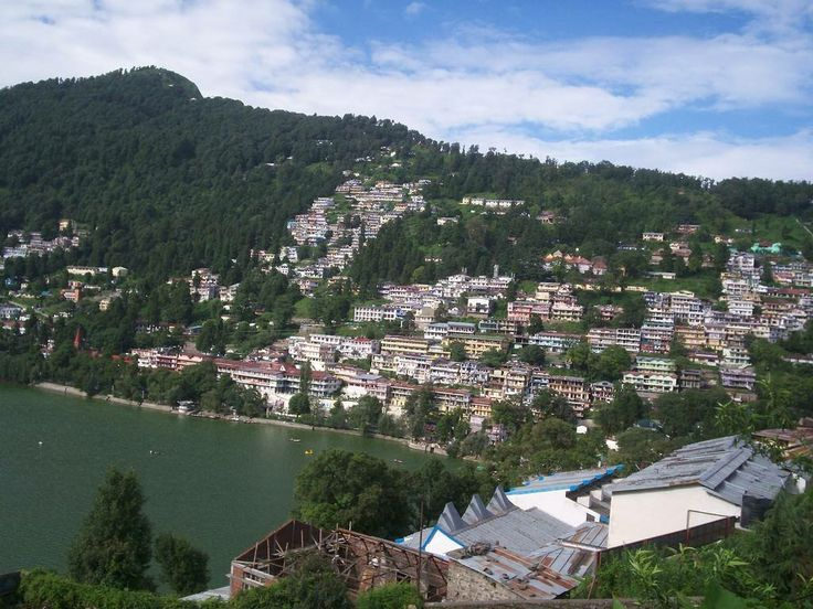 Nainital is a town in the Indian state of Uttarakhand and headquarters of Nainital district in the Kumaon foothills of the outer Himalayas. Situated at an altitude of 1,938 metres (6,358 feet) above sea level, Nainital is set in a valley containing a pear-shaped lake, approximately two miles in circumference, and surrounded by mountains, of which the highest are Naina (2,615 m (8,579 ft)) on the north, Deopatha (2,438 m (7,999 ft)) on the west, and Ayarpatha (2,278 m (7,474 ft)) on the…