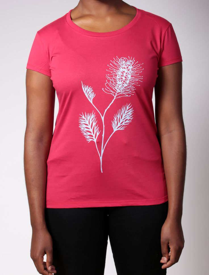 A flowering native grevillea blooms up the side of this t-shirt. Handprinted in bright turquoise onto a raspberry red organic cotton t-shirt.