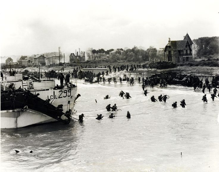Troops of the 9th Canadian Infantry Brigade (Stormont, Dundas, and Glengarry Highlanders) going ashore from LCI (L) 299 [Landing Craft Infantry], Bernières-sur-Mer, Normandy, France, 6 June 1944. Photo: Gilbert Alexander Milne/Canada. Dept. of National Defence/Library and Archives Canada/PA-122765 @ Bernières-sur-Mer, Normandy, France
