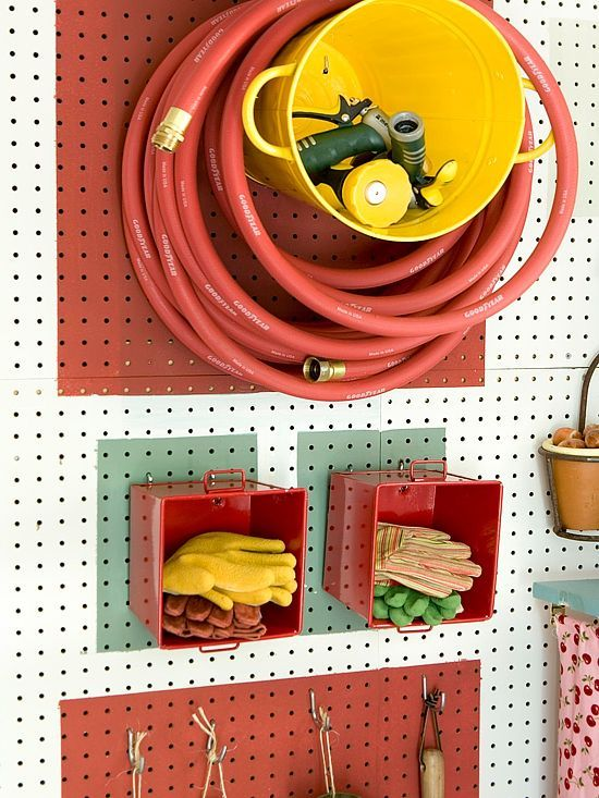 Hang the pegboard on wall stud and equip it with bins for an innovative storage system. The sideways bins stow often-used accessories that are not easily hung from hooks, such as gardening gloves and hose nozzles. Mount a large bucket to the pegboard for a modern take on a hose reel to boost function.