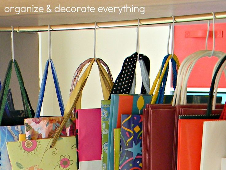 gift bag storage by Organize & Decorate Everything - I know she did this for gift bags but I'm thinking about getting some of these hooks to hang my tote bags in the closet.