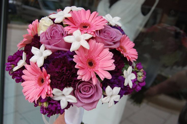 Pairing clear pink gerbera daisies with lavender roses and burgundy carnations guarantees that your bridal bouquet will make a bold statement on your wedding day. This florist punctuated the bouquet with white stephanotis flowers to up the fragrance quotient, and to share in the language of flowers that many years of marital harmony are in store for this couple.