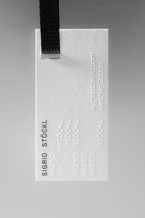 Embossed black and white branding, clothing tag.                                                                                                                                                                                 More