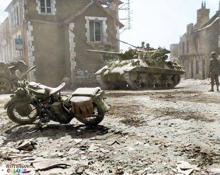 A Harley Davidson motorcycle and an M10 tank destroyer in Percy, Normandy August 1944