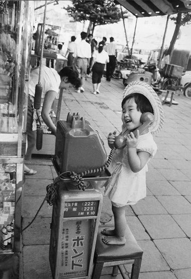 Public telephone and a girl. 1958.