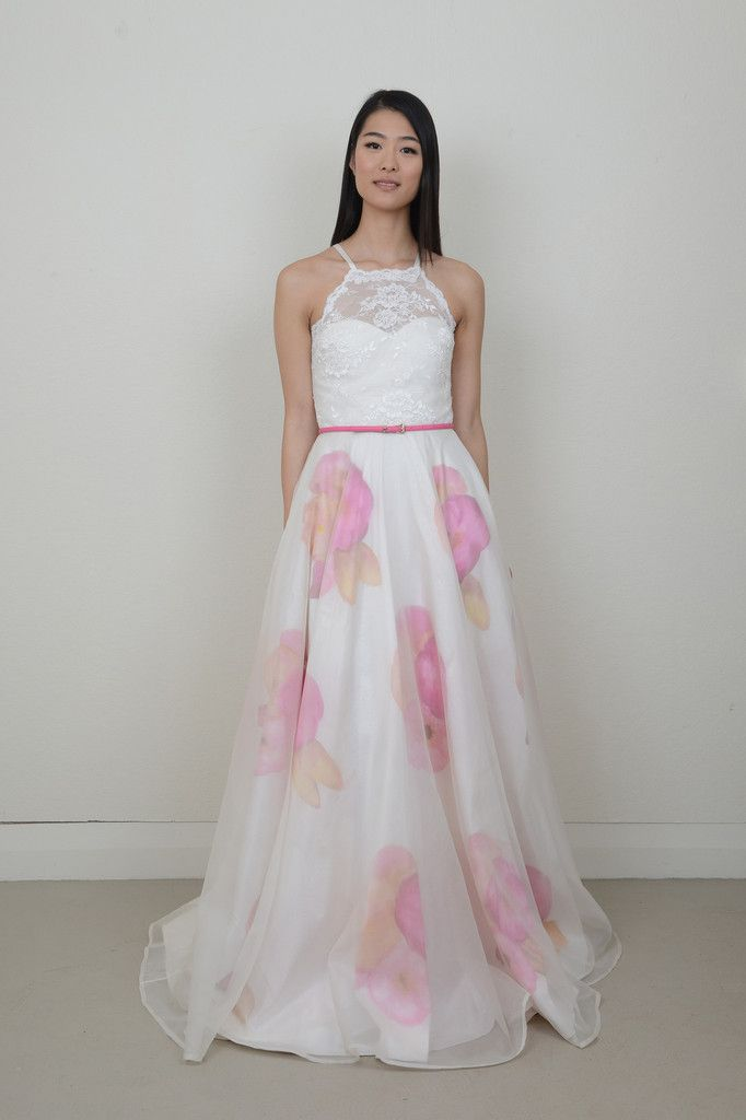 'Peering at Posies' is a bold and beautiful gown perfect for a fashionable bride. The dress features a lace halter bodice with a delicate scalloped edge and silk satin ties, while the full circle skirt has a hand painted floral motif running through, a sheer organza skirt sits over top to add depth and transparency.
