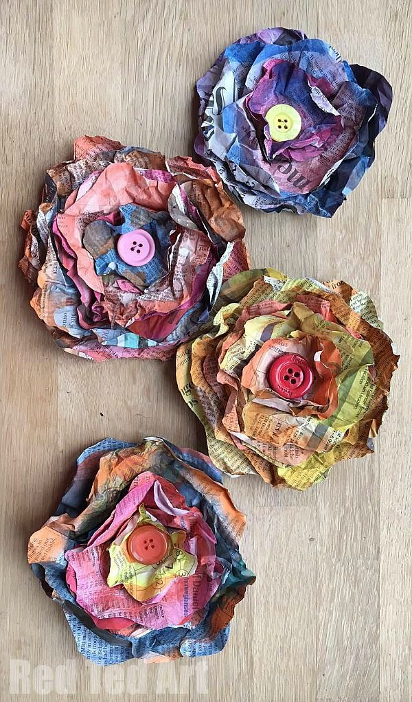 Newspaper Flowers DIY - such a super pretty chabby chic flower DIY. These are quick to make - are nice and big (or small if you prefer) and a great way to decorate quickly and inexpensively. We do love upcycled Newspaper DIYs and these watercolor newspaper flowers are just gorgeous. Love those buttons in the centre!