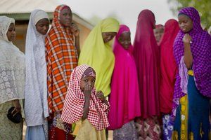 A young Nigerian girl from the Hausa tribe stands next to women queuing to validate their voting cards at a polling station located in an Islamic school in Daura. Nigerians went to the polls in presidential elections which analysts say will be the most tightly contested in the history of Africa's richest nation and its largest democracy