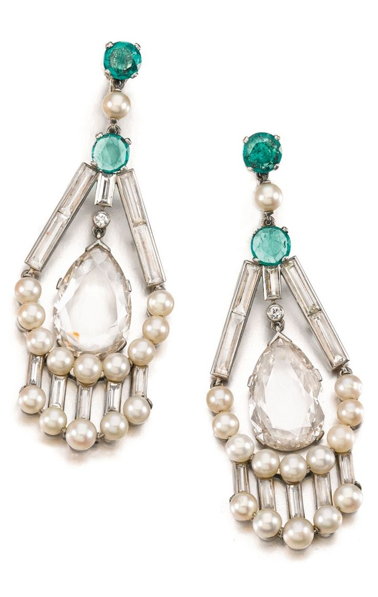 A pair of Art Deco cultured pearl, emerald and diamond ear clips, 1930s and later. Each pear-shaped diamond swing-set within a frame of baguette diamonds and cultured pearls, the surmounts set with cabochon emeralds, screw back fittings. #ArtDeco #earrings