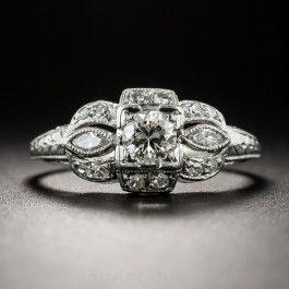 A bright and beautiful modern brilliant-cut diamond, weighing about a quarter-carat, sparkles front and center between a pair of small marquise diamonds, and is outlined all around with small glittering single-cut diamonds, all accentuated with delicate milgraining and finished with decorative hand engraving, in this distinctive and distinguished late-Art Deco engagement ring crafted in platinum. Approximately a half-carat total diamond weight. Currently ring size 4 3/4.