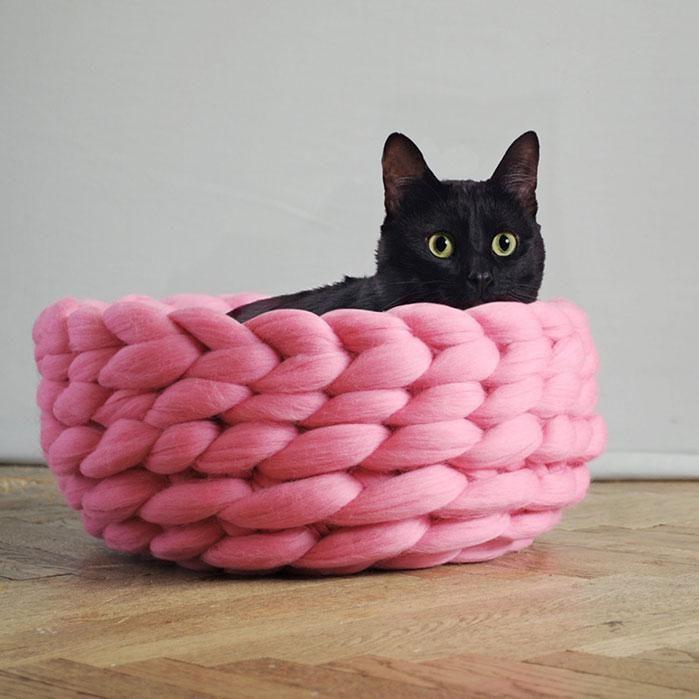 Lit pour chat en gros tricot rose avec un chat noir dedans