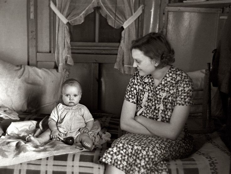 """Shantytown Baby: December 1936. Mrs. Charles Benning and baby in their shack home at Shantytown. Spencer, Iowa. 35mm negative by Russell Lee. """"It is hard for me to think of Iowa and poor people. In talking to those that lived through the 1930s, as I did, the people who lived on farms would say how poor they were then add but we had food to eat."""""""