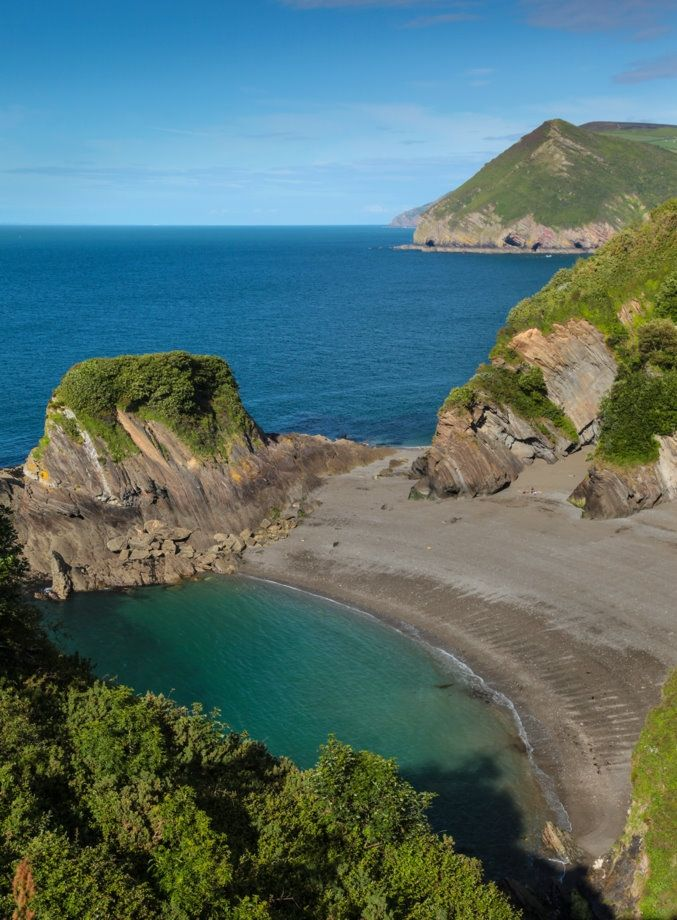 BROADSANDS BEACH, Ilfracombe, Devon, [ENGLAND] #wildbeach. Owned by Watermouth Valley Camping this crescent-shaped lagoon is not to be confused with Broadsands in Torbay. With caves and a rugged headland covered in lush vegetation this beach wouldn't look out of place in the Indian ocean. Access is by a dirt path and steep steps. In spring the cliffs are awash with wild grasses and garlic, but the beach is best in summer for maximum sunshine as it's north-facing.