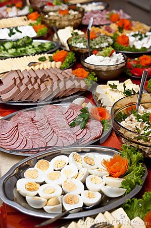 Large dishes and platters of food on an extensive food buffet table.