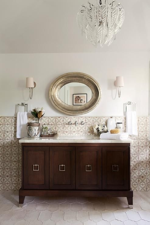 Mediterranean style bathroom features an oval silver mirror illuminated by Reed Sconces placed over a wall-mount faucet lining a cream and blue mosaic tiled wall as well as a darks tained swingle washstand placed atop a cream Moroccan tiled floor.