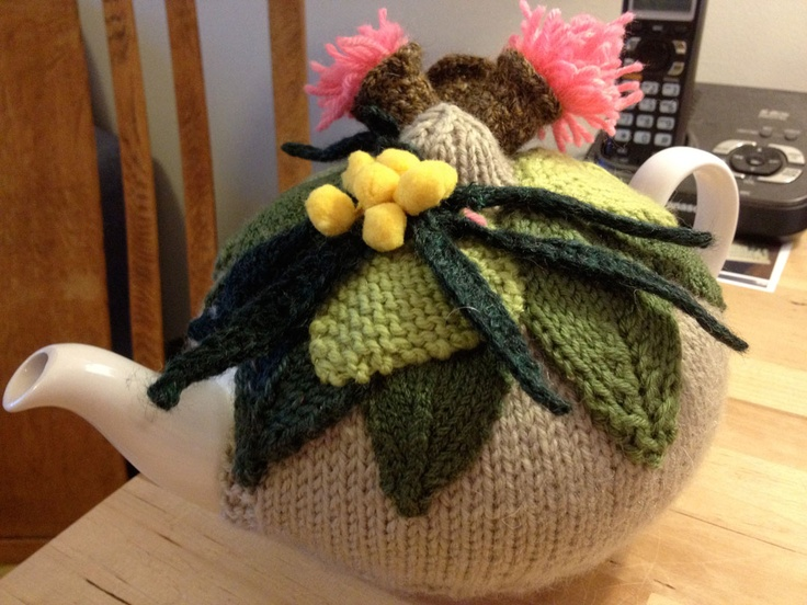 Australiana themed crochet flowers and gum nuts decorate a read cosy