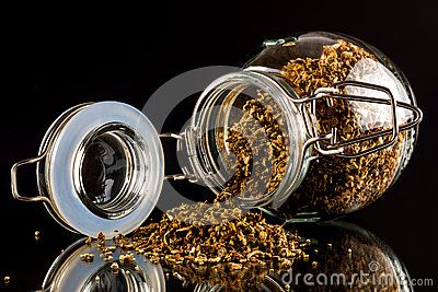 Close up of open jar of dried oregano on reflective black surface.