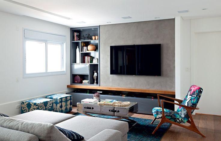 Neste living, a arquiteta Fernanda Dabbur instalou parede de drywall para a TV e para a estante. O visual limpo se deu graças ao padrão dos acabamentos, com parede de cimento queimado Terracor e estante de laca cinza brilhante