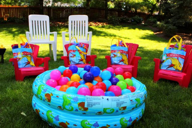 """Kids party favor for first birthday. Red plastic andorak chair with small gift bag (pool bag) that contained a rolled up beach towel, bubble maker, and sponge water """"balloons"""". Visit http://cheekychicstudio.com/2013/07/15/a-whale-of-a-time/ for more details."""