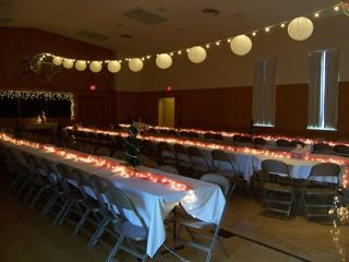 LDS  gym set up for a banquet with long tables. One strand of lights & paper lanterns. Lights down center of tables.