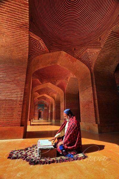 Shah Jahan Mosque, Thatta, Sidh, Pakistan | A man reading Qur'an sitting i n sun light under an Arch of Shah Jahan Mosque.