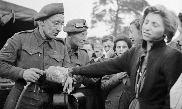 A British soldiers sprays DDT on a woman liberated from Bergen-Belsen..link to documentary info
