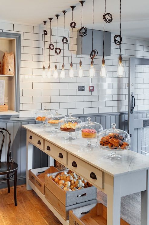 Bistro kitchen boasts white subway tiled upper walls over gray beadboard lower walls which highlight a long white freestanding island accented with oil-rubbed bronze cup pull hardware and a white marble counter which is illuminated by a row of edison bulb pendant lights.