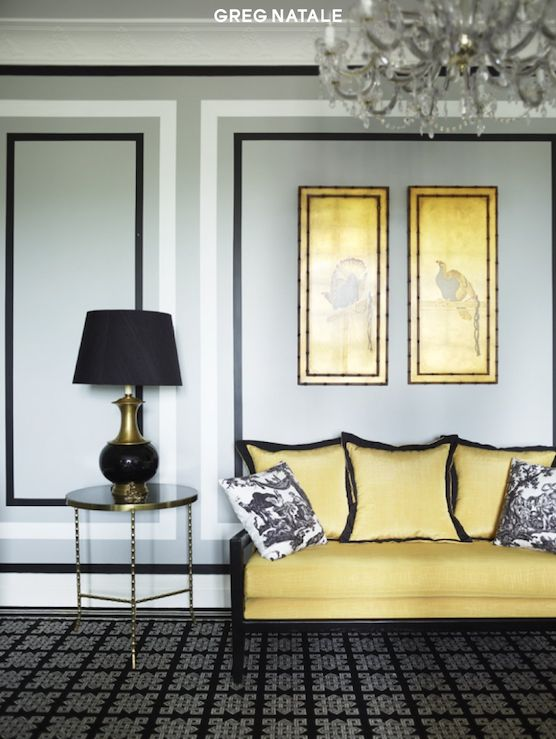 Greg Natale  Chic black & yellow living room design with gray walls, brass accent table, black geometric rug, yellow & black settee & silk pillows, white & black toile pillows and black lamp.