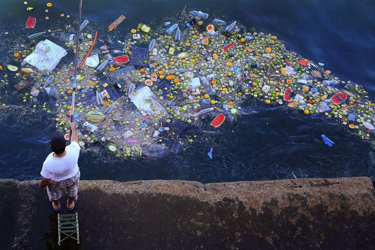A man holds a fishing rod as floating trash hits the coastline of the Mediterranean Sea in Beirut, Lebanon, Thursday, Sept. 29, 2016. (AP Photo/Hassan Ammar