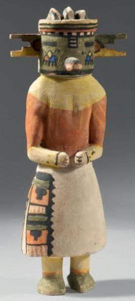 Tugwunag kachina tihu (cumulus cloud) Hopi, circa 1950 (Colton #97) [jcx] Bois de cottonwood, pigments, cordelette Circa 1950 Hauteur: 31cm Le masque est surmonté de trois ailettes verticales qui répondent à la forme très découpée des oreilles. Le front est peint d'un arc en ciel surplombant une frise de carrés noirs et blancs. Le nez en «bec de canard» est placé sous une patte verticale de rectangles blancs soulignés au trait noir. Le masque vert est orné sur les joues du signe du nuage. Le…