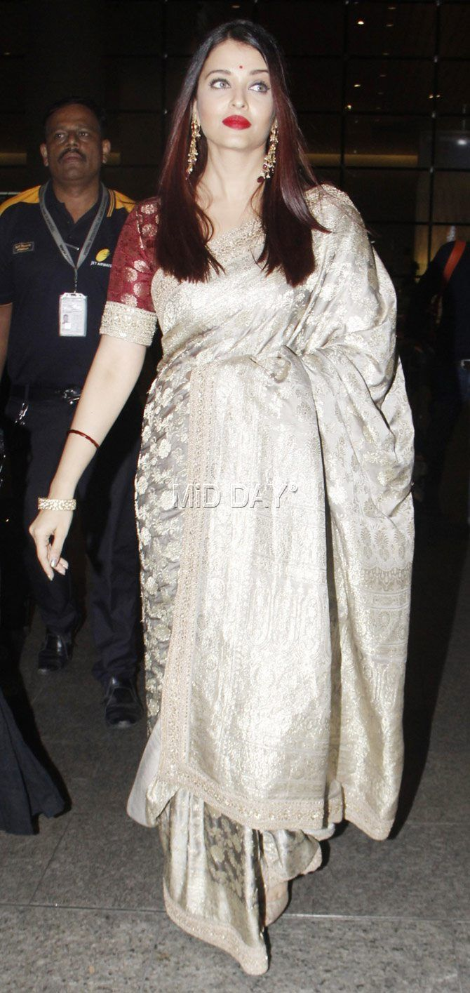 Aishwarya Rai Bachchan looked gorgeous in a Sabyasachi metallic grey traditional weave saree, which she teamed up with a maroon blouse. r