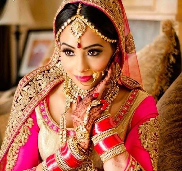 The Punjabi Bridal Look   Oh, the glamour of this beautiful bride! She totally rocks this hot pink, gold-embroidered lehenga. Her eye makeup has been done exceptionally well