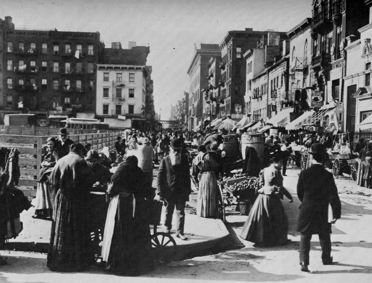 An American Gilded Age view of: shoppers  purchasing goods from pushcart vendors on Hester Street, late 19th-century. Located on the Lower East Side of Manhattan, c.1898. ~ {cwlyons}