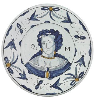 A BRISLINGTON DELFT ROYAL PORTRAIT CHARGER OF QUEEN MARY CIRCA 1689 Painted in blue and outlined in manganese with a shoulder length portrait of Queen Mary with an ochre necklace and earrings, flanked by the manganese initials QM, the border with stylised flowers and foliage suspended from tied ribbons, the underside with buff slip with a lead glaze, the footrim pierced for hanging 13¼ in.