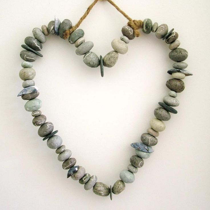 Handmade clay pebbles are threaded onto wire alongside beach combed Cornish slate and mussel shells to make this lovely hanging heart.