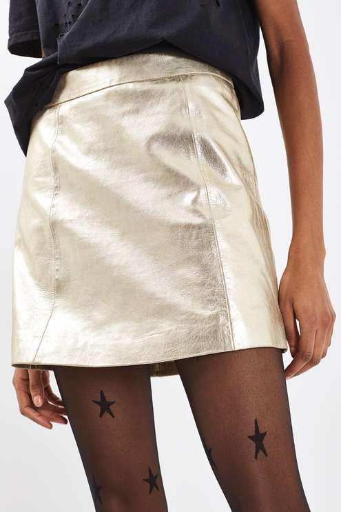 It's all about the trophy skirt this party season – invest in yours with this striking gold style. Sitting high on the waist, it comes in a flattering a-line shape. We've styled with a band tee and star-print tights for a stand-out style.  #Topshop