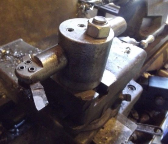 """Boring Bar and Tool Post by Frank S -- Before I got my Aloris quick change tool post for the little Craftsman lathe I found myself needing a tool post for a boring bar to do a small job I had.  Here is what I did I grabbed a 2 1/2"""" long piece of 2 1/2"""" round that happened to be laying under my band saw.  I surarred the ends then un scrolled the jaws from the chuck when I returned them I put the #3 jaw 2 groves out of time then chucked the part again this time it was off center enough to..."""