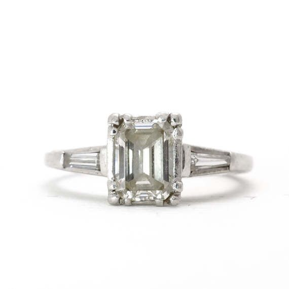 Vintage Emerald Cut Engagement Ring | Platinum | Diamond | Handmade | Art Deco  This classic handmade emerald cut diamond ring is well balanced with a sophisticated clean look. The vintage emerald cut diamond is approximately 0.73 carats, VS2 clarity, F-G colour with very good cut (6.20 x 4.70 x 2.63 mm). The center emerald cut diamond is framed by two lovely claw set tapered baguette cut diamonds weighing a total 0.20 carats, VS1 clarity, F-G colour with a good cut (measuring 4.00 x. 1.80 x…