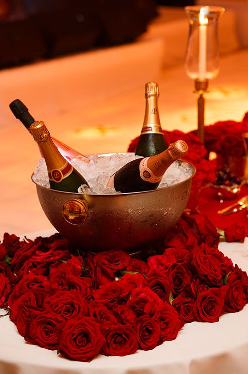 Bottles Of Champagne Rest In A Silver Bowl Surrounded By Fresh Red